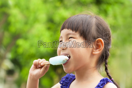 happy little girl eating popsicle at