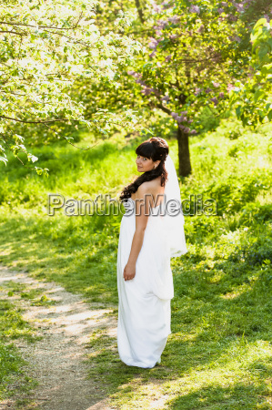 brunette bride walking on path under
