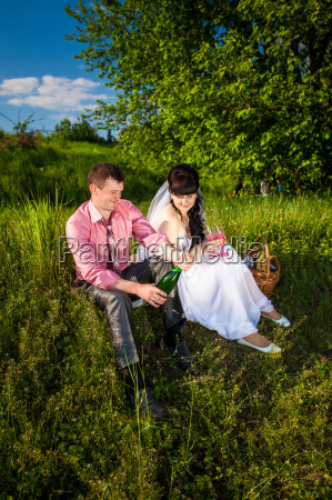groom opens champagne at picnic in