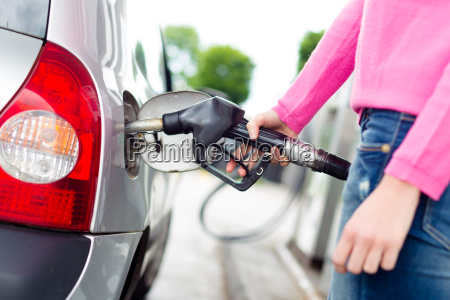 lady pumping gasoline fuel in car
