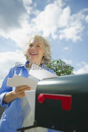 smiling senior woman mail letter bill