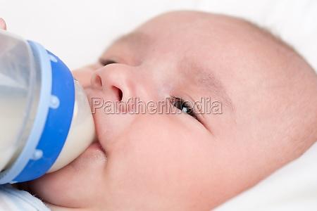 baby drinks milk from bottle