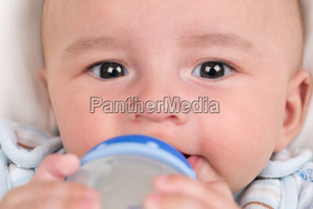 baby drinks milk and holds the