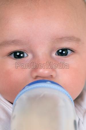 baby drinks milk from vials