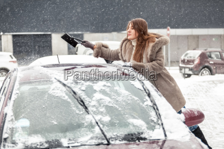 young woman cleaning snow from car