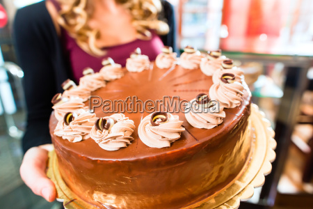 female baker presenting cake in confectionery