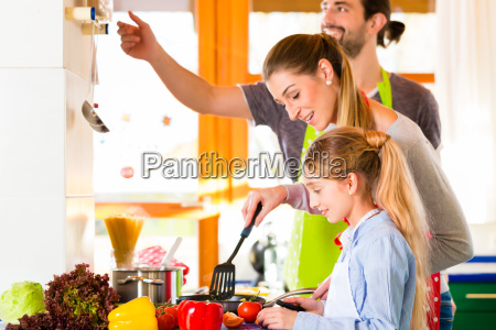 family cooking in domestic kitchen healthy