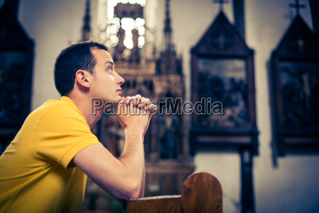 handsome young man praying in a