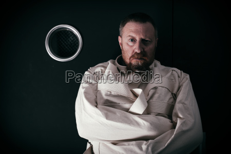 insane man in a cell wearing