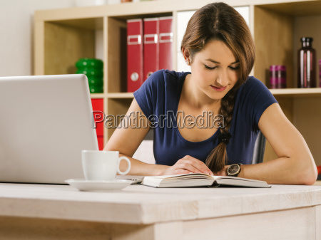 woman reading a book and using
