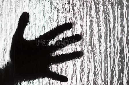 human hand behind textured glass