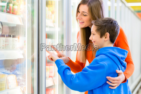 family selecting cooled products in hypermarket