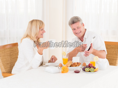 mature couple using and pointing at