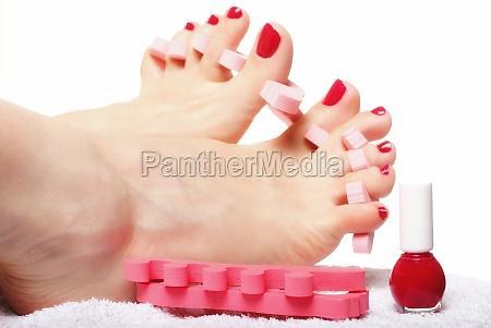 foot pedicure applying red toenails on