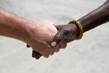 hand greeting between a caucasian and