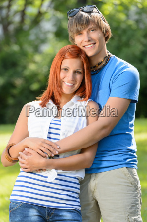 romantic teenage couple hugging in sunny