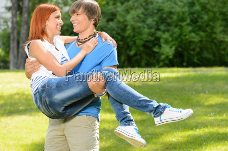 teenage boyfriend carry girlfriend in his