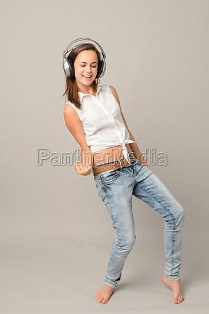 dancing girl with headphones singing enjoy