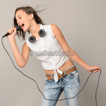 singing teenage girl with microphone karaoke