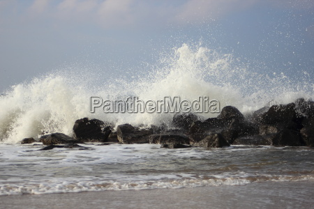 waves breaking against large stones at