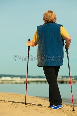 active senior woman nordic walking on