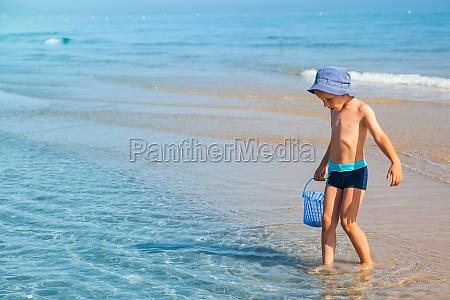 boy looking for sea shells