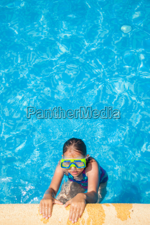 happy girl with goggles in swimming