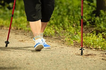 active senior woman nordic walking in