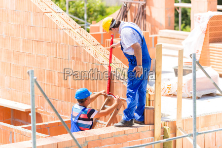 craftsmen control walls on building site