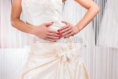 woman tasting wedding dress in store