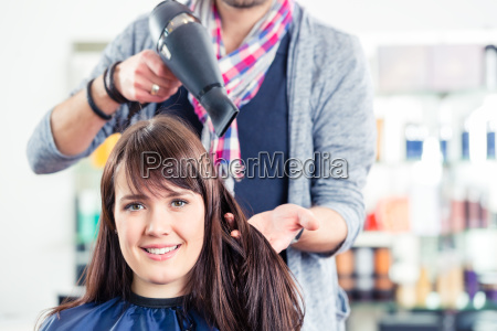 barber foehnt womans hair in salon