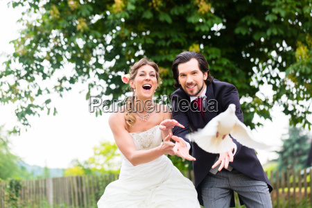 newlyweds with flying white doves