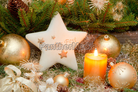 golden christmas decoration with burning candle