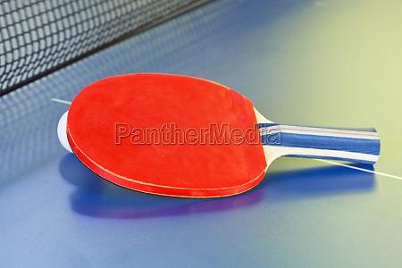red bat tennis ball on blue