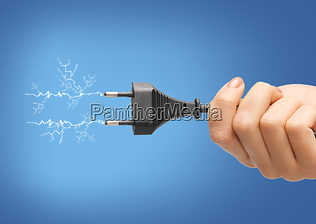 hand holding black electrical plug with