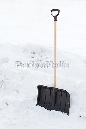 black snowshowel with wooden handle in