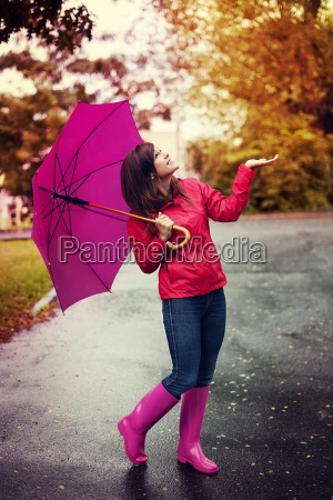 happy woman with umbrella checking for