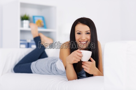 woman relaxing on couch with cup