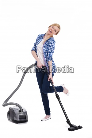 pretty and smiling woman vacuuming a