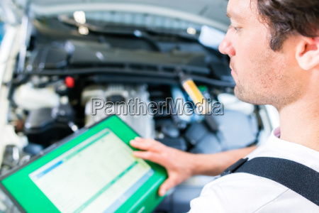 car mechanic with diagnostic equipment in