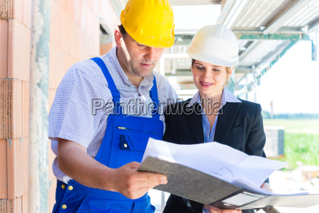 team inspects construction plans at a