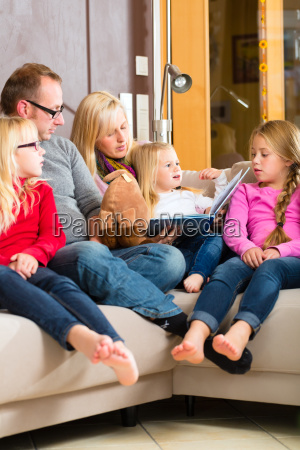 family sitting together on the sofa