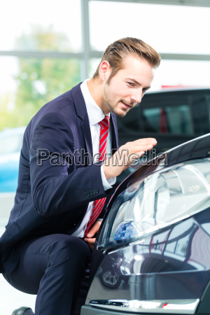 sellers with car in car dealership