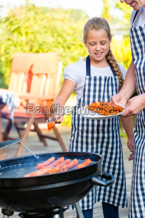 father and daughter grilling together on