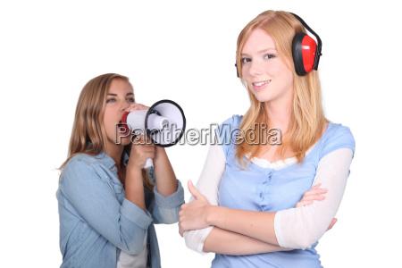 girl shouting in loudspeaker at female