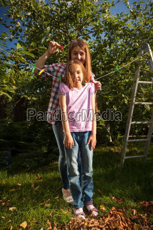 mother hanging daughter on string with