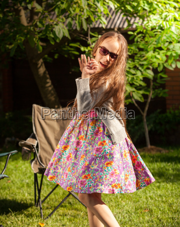 young girl in sunglasses dancing at