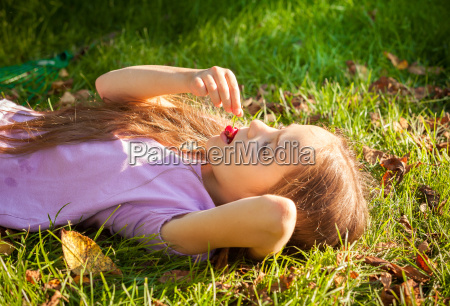 young girl lying on grass and