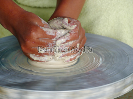 hands making pottery on the potters