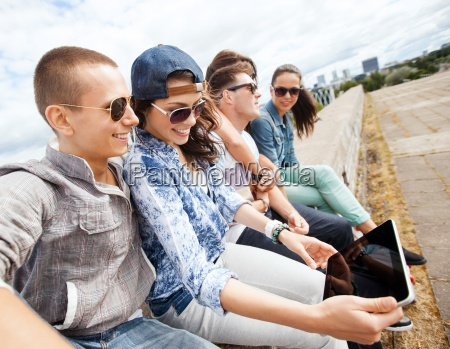 group of teenagers looking at tablet
